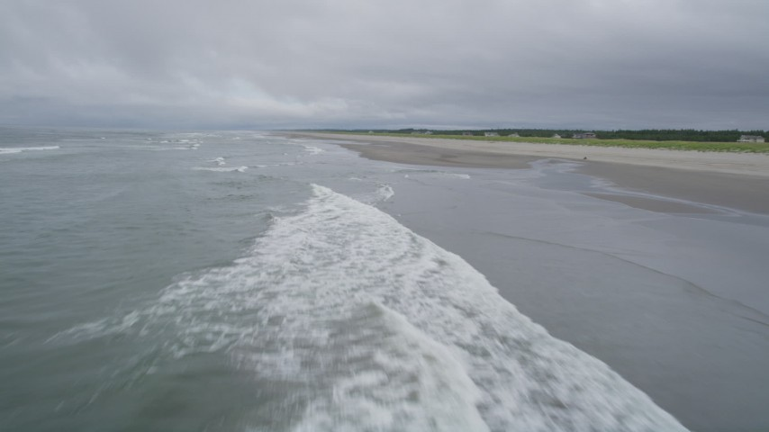 5K stock footage aerial video fly low over ocean waves and an empty beach in Long Beach, Washington Aerial Stock Footage | AX56_141