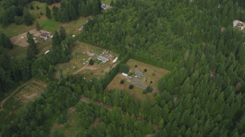 5K stock footage aerial video tilt to a bird's eye view of rural homes and evergreen trees in Grapeview, Washington Aerial Stock Footage AX58_013 | Axiom Images