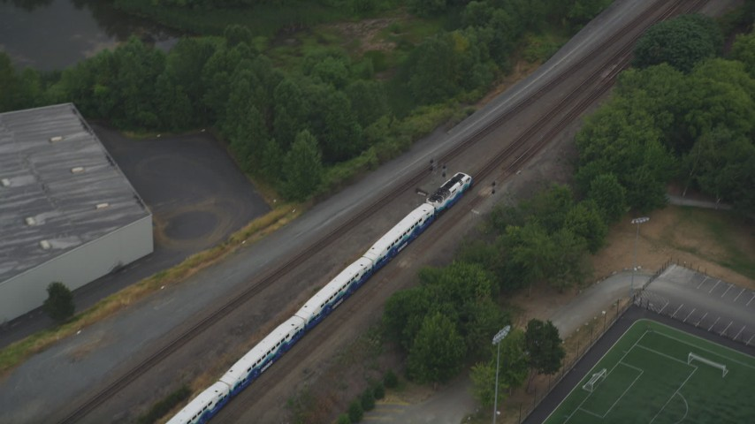 5K stock footage aerial video of tracking a commuter train through Tukwila, Washington Aerial Stock Footage | AX58_077