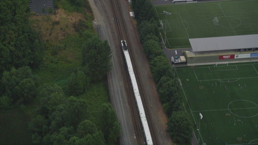 5K stock footage aerial video of tracking a commuter train passing through Tukwila, Washington Aerial Stock Footage | AX58_078