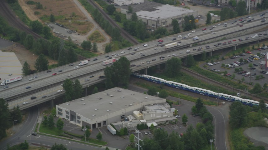 5K stock footage aerial video of tracking a commuter train running beneath a freeway in Tukwila, Washington Aerial Stock Footage | AX58_079