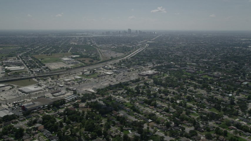 5K aerial video fly over Gentilly to approach stores by the I-10, with Downtown New Orleans in the background, Louisiana Aerial Stock Footage | AX59_001