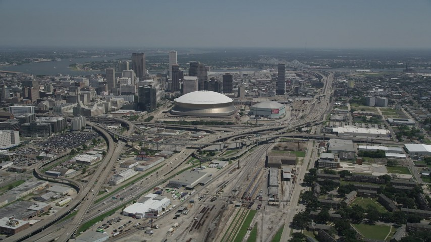 5K aerial video approach the freeway interchange by the Superdome, and Downtown New Orleans skyscrapers, Louisiana Aerial Stock Footage AX59_039
