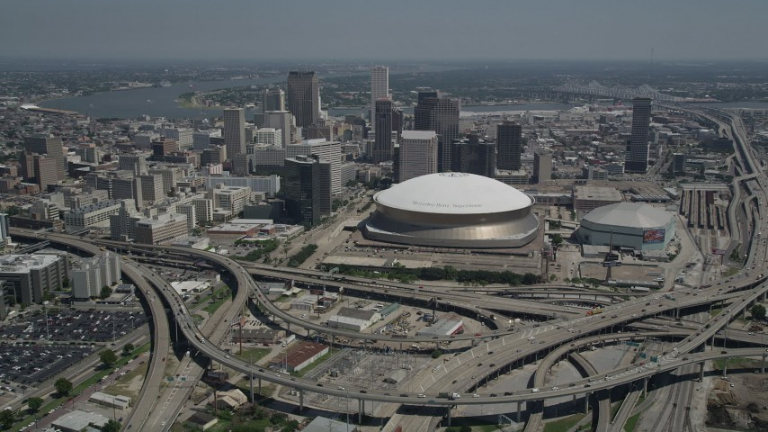 5K stock footage aerial video fly over freeway interchange to approach Superdome, Downtown New Orleans skyscrapers in Louisiana Aerial Stock Footage | AX59_040