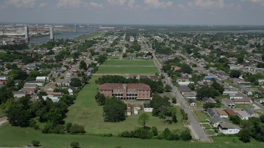 5K aerial video fly over abandoned school to approach homes in the Lower Ninth Ward, New Orleans, Louisiana Aerial Stock Footage | AX59_056