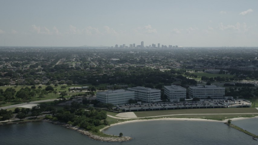 5K stock footage aerial video of office buildings by Lake Pontchartrain, and view of Downtown New Orleans skyline, Louisiana Aerial Stock Footage | AX60_002