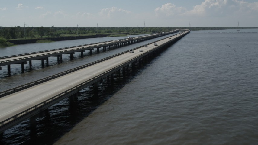5K aerial video of Interstate 10 with light traffic on the shore of Lake Pontchartrain in Norco, Louisiana Aerial Stock Footage | AX60_006