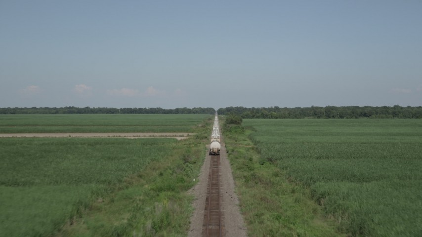 5K stock footage aerial video of following railroad tracks to chase a train passing sugar cane fields, Vacherie, Louisiana Aerial Stock Footage | AX60_061