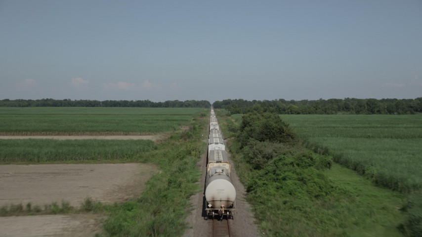 5K stock footage aerial video approach the end of a train and fly over several rail cars in Vacherie, Louisiana Aerial Stock Footage | AX60_062