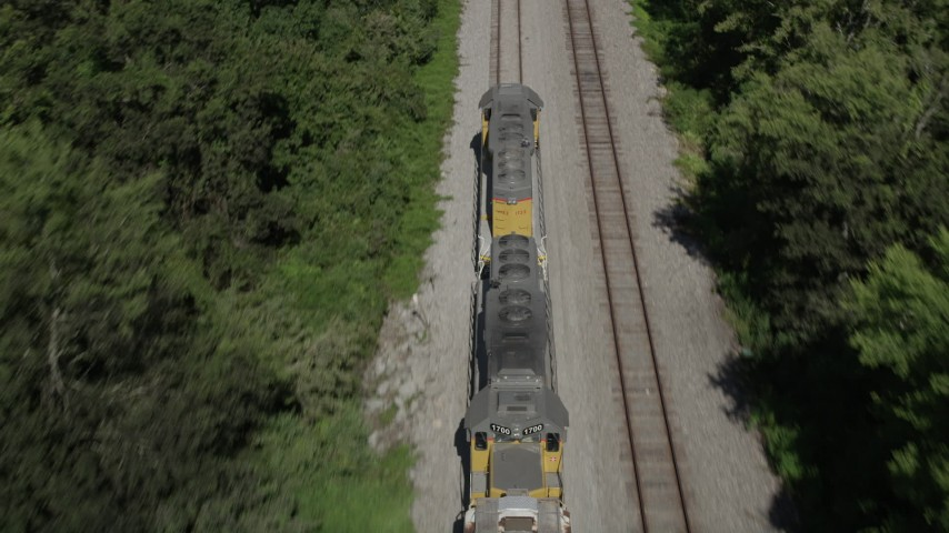 5K stock footage aerial video tilt and track the engine of a train running between trees in Edgard, Louisiana Aerial Stock Footage | AX60_066