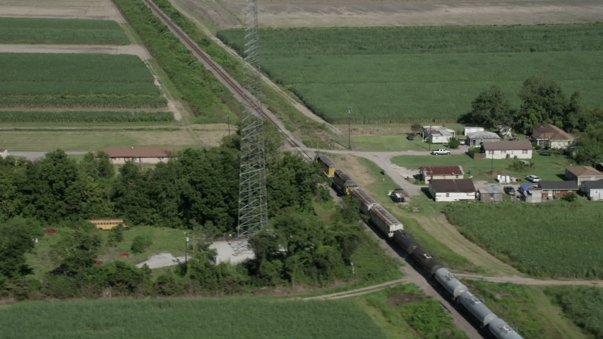 5K stock footage aerial video of tracking a train speeding past rural homes and sugar cane fields, Edgard, Louisiana Aerial Stock Footage | AX60_070