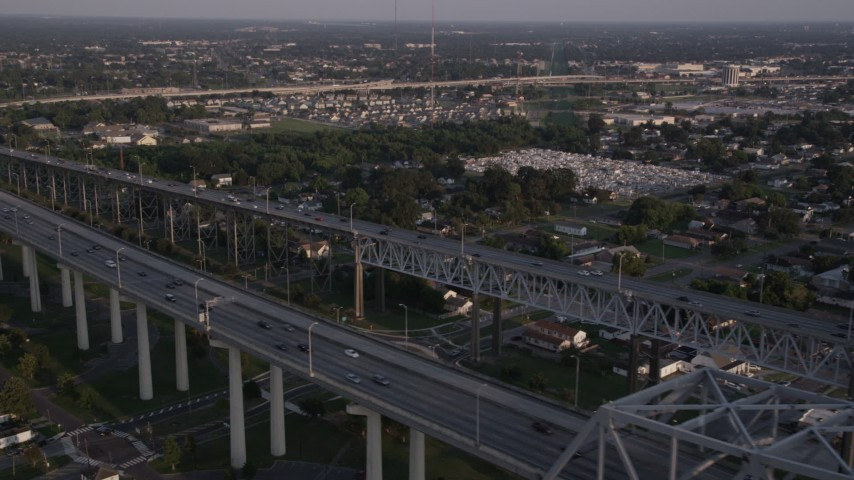 5K stock footage aerial video fly over the convention center to track cars on Crescent City Connection Bridge at sunset, New Orleans, Louisiana Aerial Stock Footage AX61_020 | Axiom Images