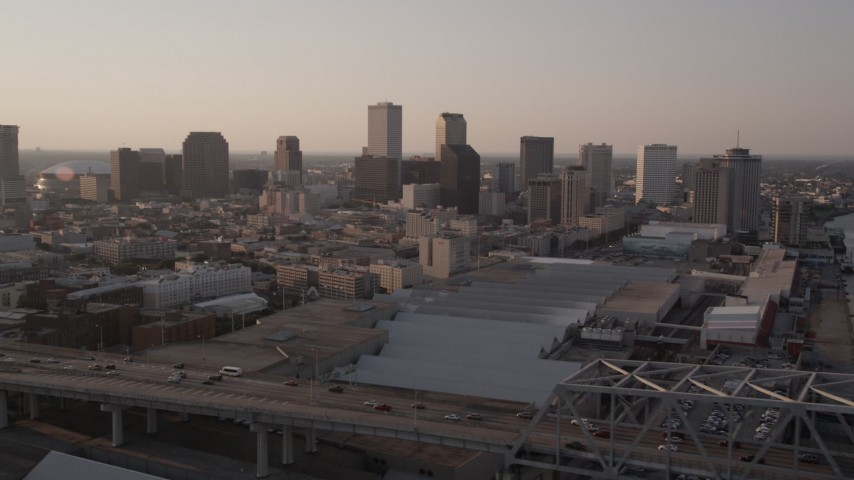 5K aerial video flyby Crescent City Connection Bridge at sunset to focus on Downtown New Orleans, Louisiana Aerial Stock Footage | AX61_022