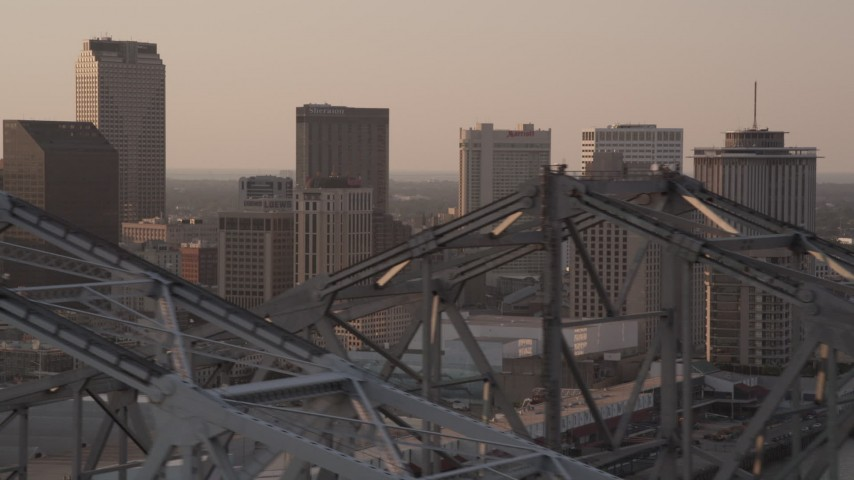 5K aerial video fly over Crescent City Connection, and focus on skyscrapers, Downtown New Orleans, Louisiana, sunset Aerial Stock Footage | AX61_025