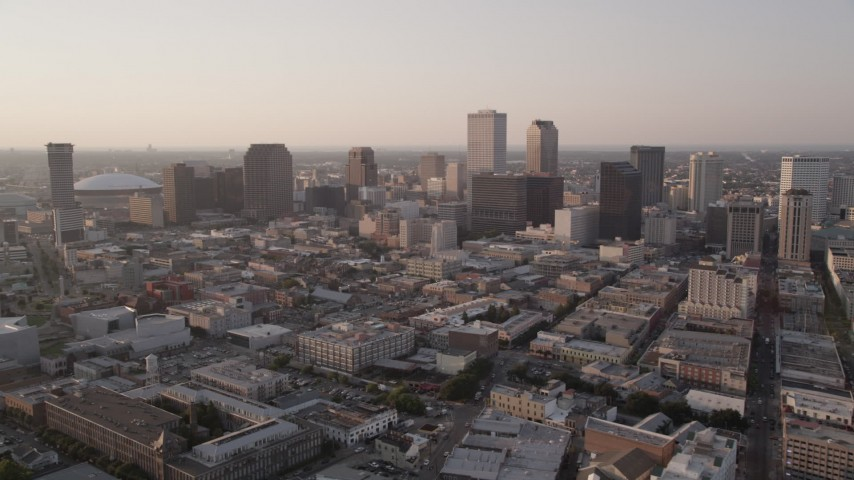 5K aerial video flyby skyscrapers and approach the Plaza Tower at sunset in Downtown New Orleans, Louisiana Aerial Stock Footage | AX61_026