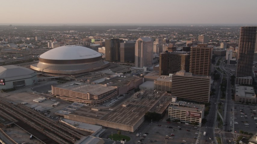 5K stock footage aerial video flyby Plaza Tower to approach Superdome and New Orleans Arena at sunset, New Orleans, Louisiana Aerial Stock Footage | AX61_027
