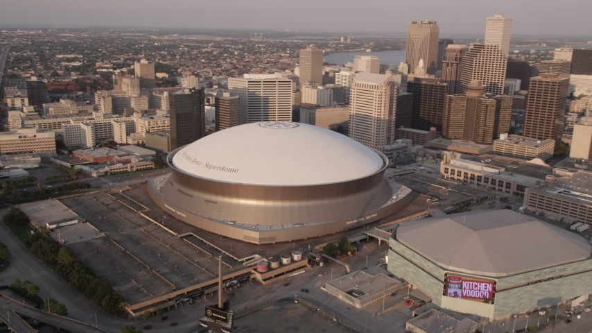 5K aerial video track Superdome, reveal Downtown New Orleans skyscrapers, Louisiana, sunset Aerial Stock Footage | AX61_028