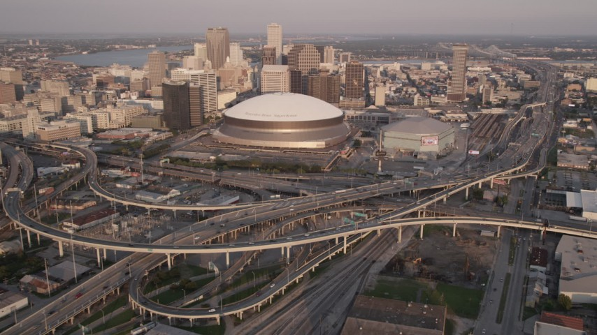 5K stock footage aerial video reverse view of Superdome and Downtown New Orleans skyscrapers at sunset, Louisiana Aerial Stock Footage | AX61_029