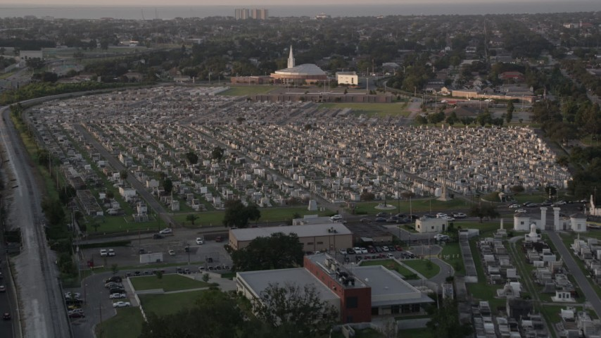 5K stock footage aerial video fly over Greenwood Cemetery tombs and approach the church at sunset, New Orleans, Louisiana Aerial Stock Footage | AX61_031