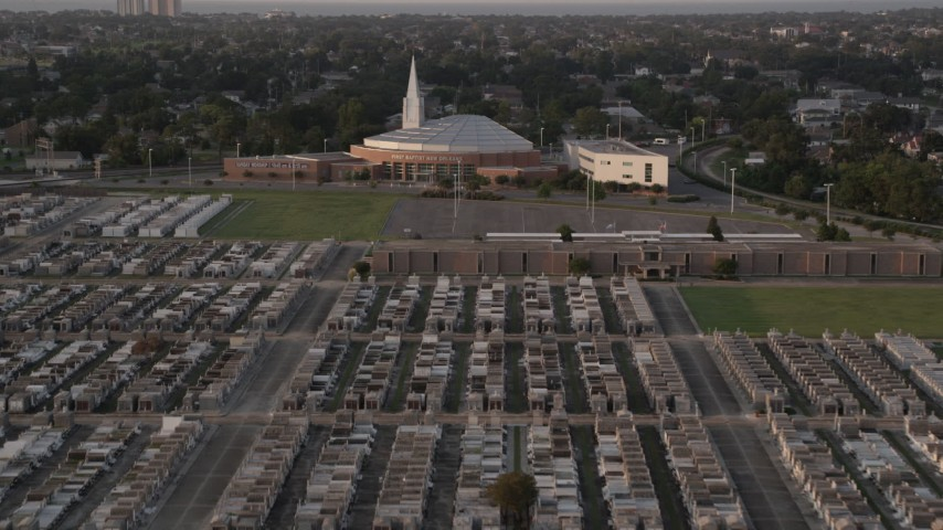 5K stock footage aerial video fly over Greenwood Cemetery toward First Baptist New Orleans Church at sunset, Louisiana Aerial Stock Footage | AX61_032
