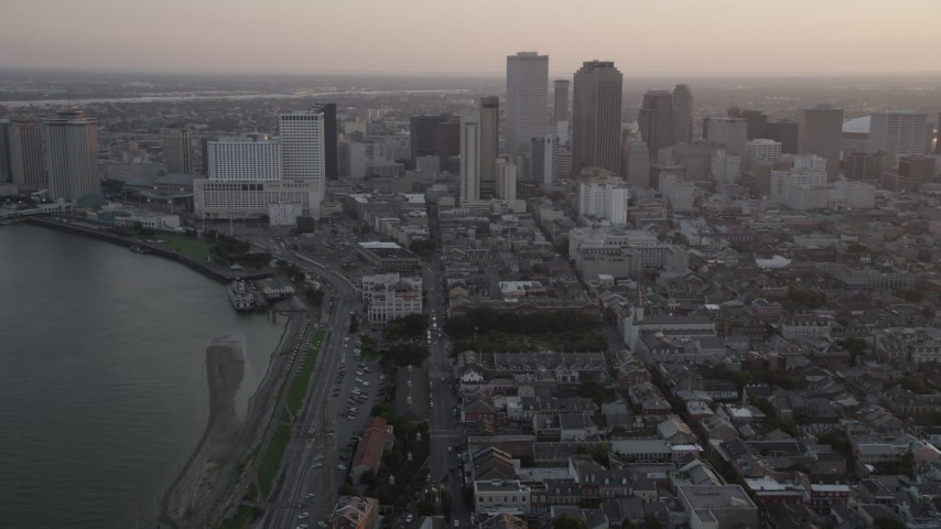 5K stock footage aerial video of Downtown New Orleans at sunset, seen from the French Quarter and the Mississippi River, Louisiana Aerial Stock Footage | AX61_050