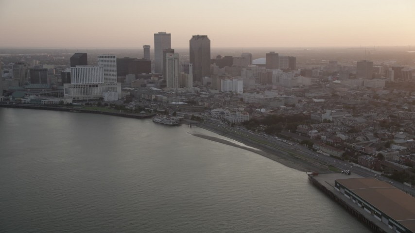5K aerial video of Downtown New Orleans skyscrapers at sunset, seen from the Mississippi River, Louisiana Aerial Stock Footage | AX61_051