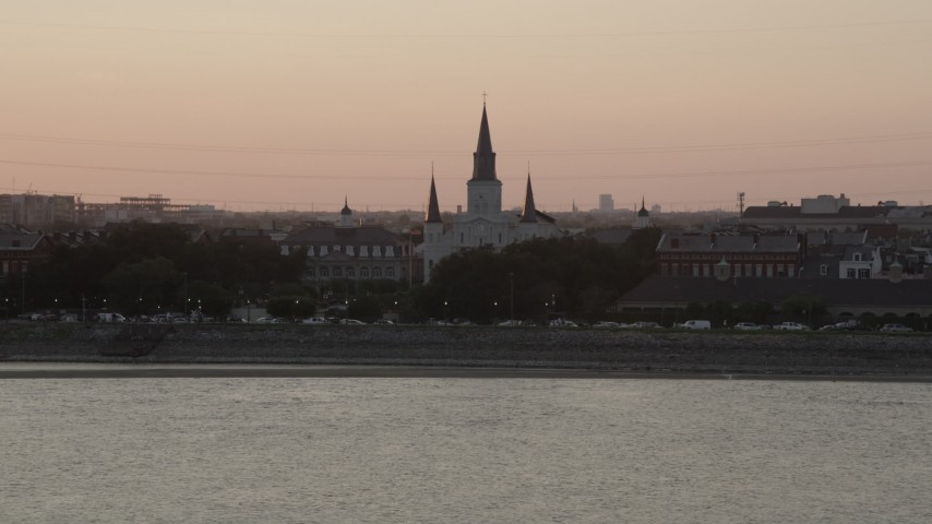 5K stock footage aerial video approach St. Louis Cathedral from the Mississippi River at sunset, French Quarter, New Orleans, Louisiana Aerial Stock Footage | AX61_056