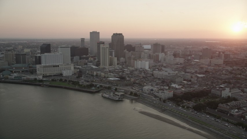5K stock footage aerial video of skyscrapers in Downtown New Orleans seen from the Mississippi River at sunset, Louisiana Aerial Stock Footage | AX61_063