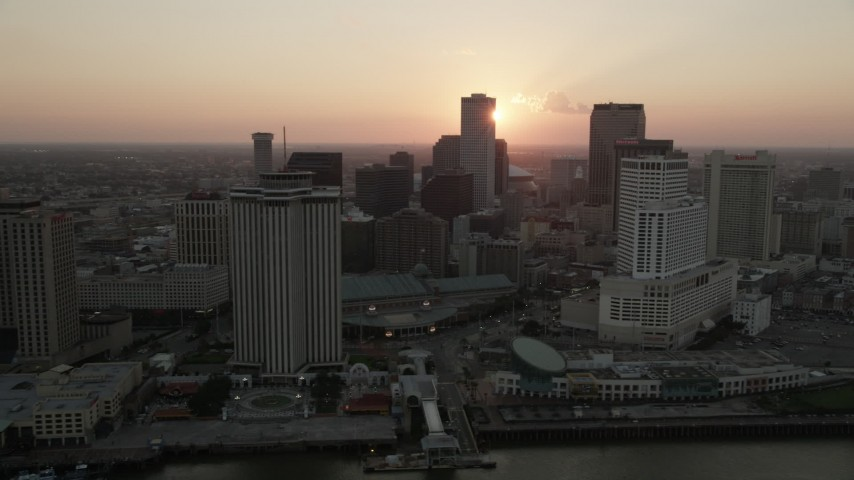 5K stock footage aerial video pass riverfront hotels and skyscrapers in Downtown New Orleans with the setting sun in the background, Louisiana Aerial Stock Footage | AX61_064