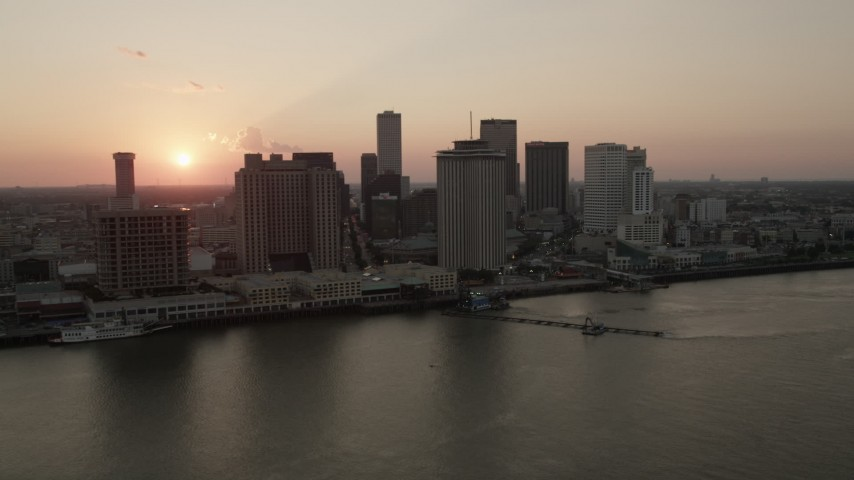 5K stock footage aerial video of the setting sun behind Downtown New Orleans skyscrapers, Louisiana Aerial Stock Footage | AX61_066