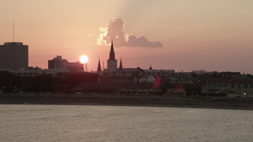 5K stock footage aerial video of St. Louis Cathedral in the French Quarter of New Orleans, seen from the river at sunset, Louisiana Aerial Stock Footage | AX61_068