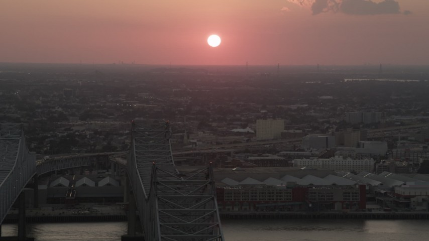 5K stock footage aerial video of the setting sun seen from Crescent City Connection Bridge at sunset, New Orleans, Louisiana Aerial Stock Footage | AX61_069
