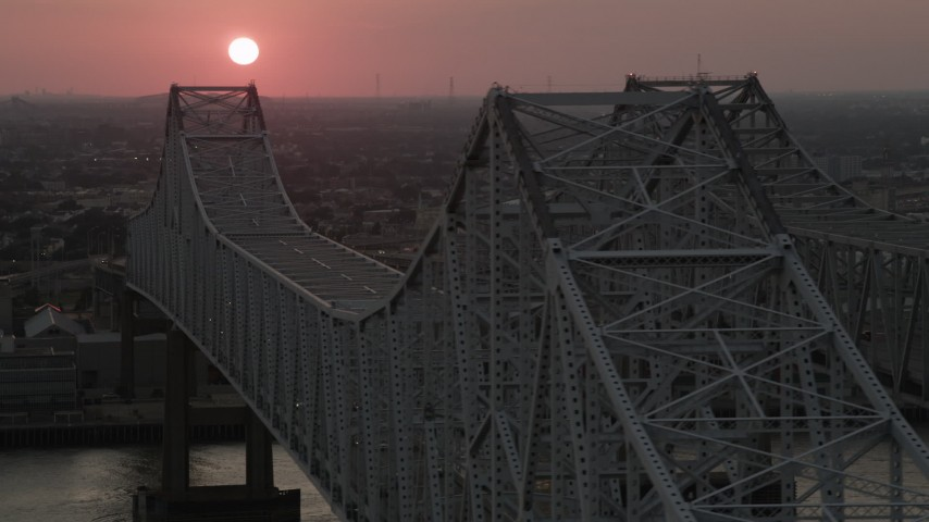 5K aerial video of light traffic on the Crescent City Connection Bridge and setting sun in the background, New Orleans, Louisiana Aerial Stock Footage | AX61_070