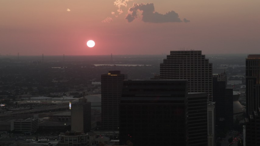 5K aerial video of the setting sun behind Plaza Tower and Downtown New Orleans, Louisiana Aerial Stock Footage | AX61_071