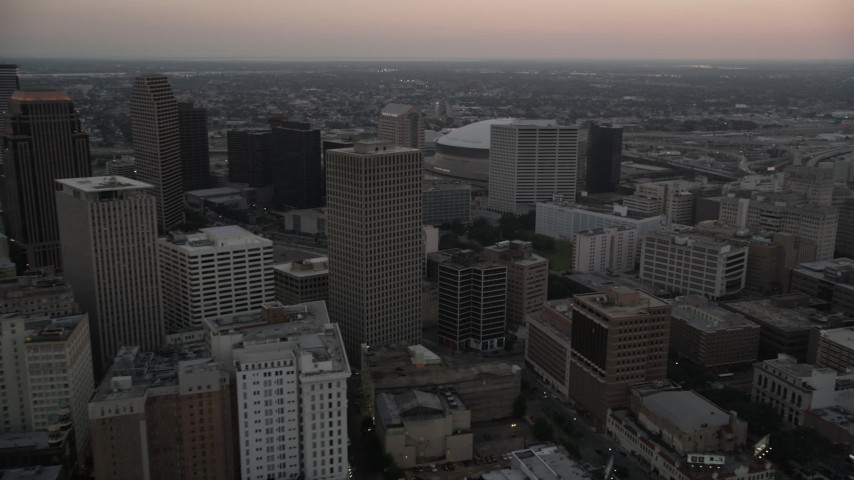 5K aerial video of passing high-rises and skyscrapers in Downtown New Orleans at sunset, Louisiana Aerial Stock Footage | AX61_072