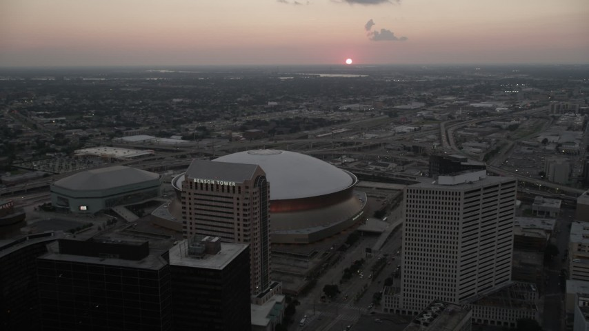 5K stock footage aerial video fly over Superdome and approach freeway interchange at sunset, New Orleans, Louisiana Aerial Stock Footage | AX61_075