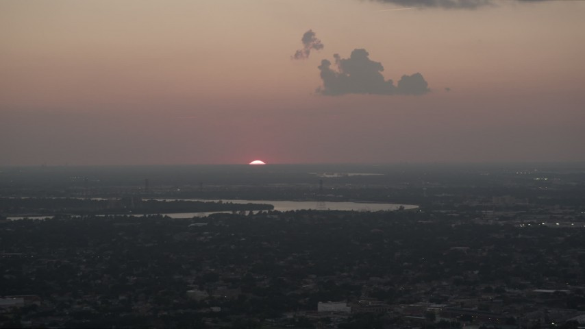 5K stock footage aerial video of the setting sun dipping below the horizon beyond the Mississippi River and Carrollton, Louisiana Aerial Stock Footage | AX61_078