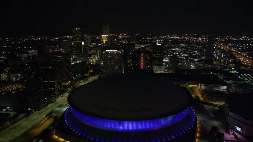 5K stock footage aerial video fly over the Superdome at night and approach skyscrapers in Downtown New Orleans, Louisiana Aerial Stock Footage | AX62_006