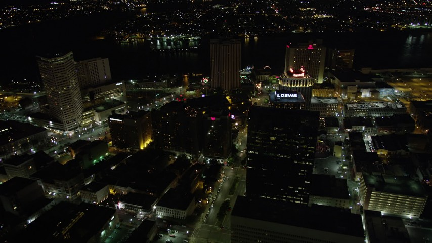 5K stock footage aerial video follow Poydras Street to hotels in Downtown New Orleans at night, Louisiana Aerial Stock Footage | AX62_008