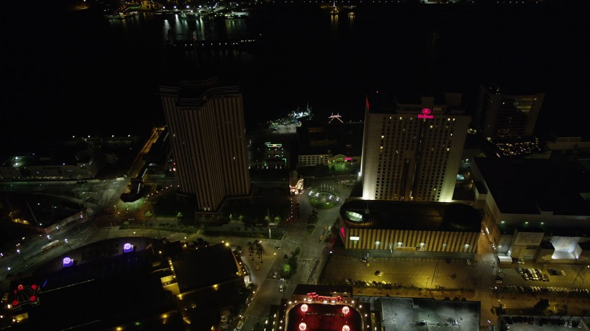 5K stock footage aerial video fly over Harrah's Casino to approach World Trade Center and Hilton Riverside at night, Downtown New Orleans, Louisiana Aerial Stock Footage | AX62_009