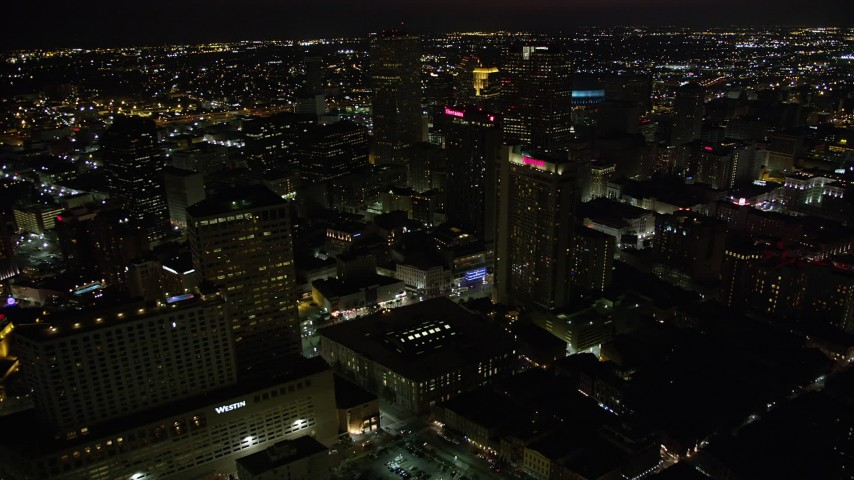 5K stock footage aerial video fly over Marriott and Sheraton hotels to approach Place St Charles at night, Downtown New Orleans, Louisiana Aerial Stock Footage | AX62_010