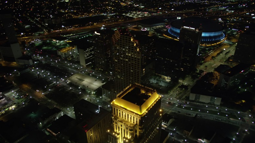 5K aerial video fly over skyscrapers and approach the Superdome in Downtown New Orleans at night, Louisiana Aerial Stock Footage | AX62_011