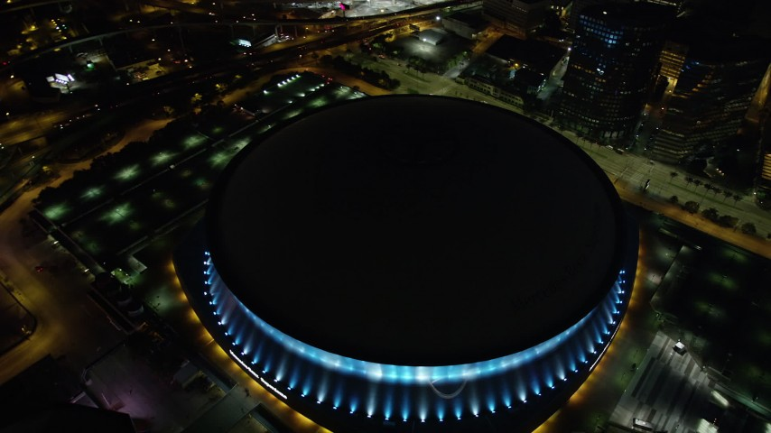 5K stock footage aerial video orbit the Superdome at night as lights change color, Downtown New Orleans, Louisiana Aerial Stock Footage | AX62_012