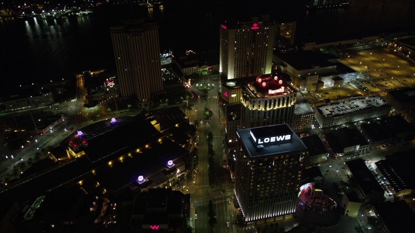 5K stock footage aerial video follow Poydras Street past hotels in Downtown New Orleans at night, Louisiana Aerial Stock Footage | AX62_014