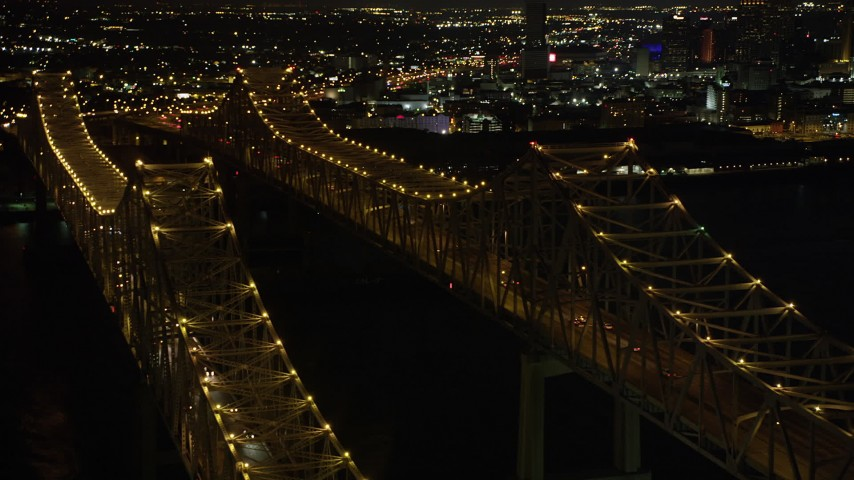 5K stock footage aerial video orbit light traffic on the Crescent City Connection Bridge at night, New Orleans, Louisiana Aerial Stock Footage | AX62_016