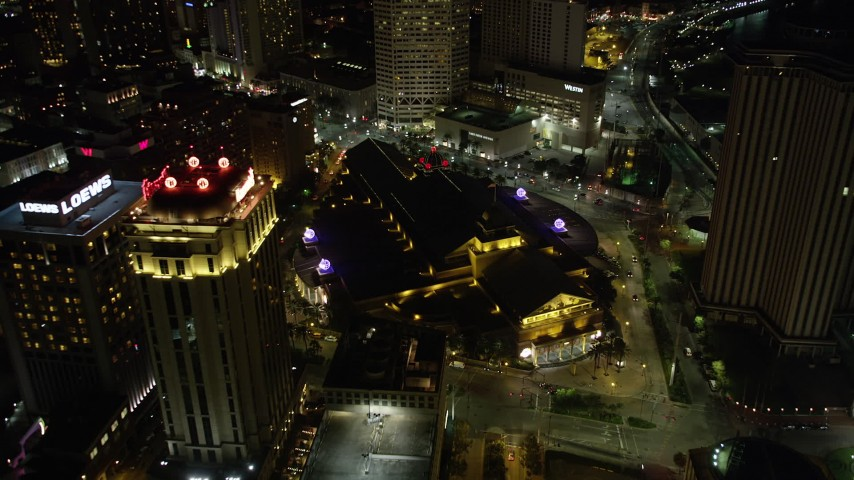 5K aerial video follow Convention Center Boulevard to approach hotels and Harrah's casino in Downtown New Orleans at night, Louisiana Aerial Stock Footage | AX62_018
