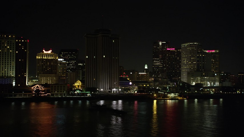 5K aerial video of low altitude view of riverfront skyscrapers in Downtown New Orleans at night, Louisiana Aerial Stock Footage | AX62_031