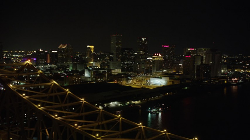 5K stock footage aerial video reverse view of Downtown New Orleans at night, reveal Crescent City Connection, Louisiana Aerial Stock Footage | AX62_032