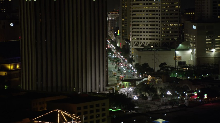 5K stock footage aerial video track Harrah's New Orleans and reveal Canal Street at night, Downtown New Orleans, Louisiana Aerial Stock Footage | AX62_038