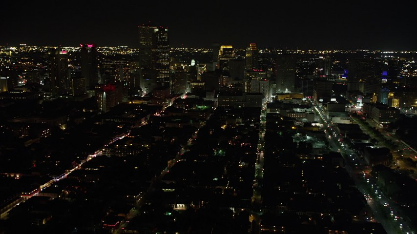 5K stock footage aerial video of Bourbon Street and Downtown New Orleans at night seen from the French Quarter, Louisiana Aerial Stock Footage | AX62_040